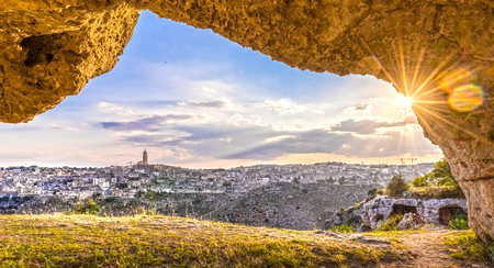 rupestrian: Panoramic view through cave of sassi di Matera,basilicata, Italy. UNESCO European Capital of Culture 2019 under blue sky and sun flare