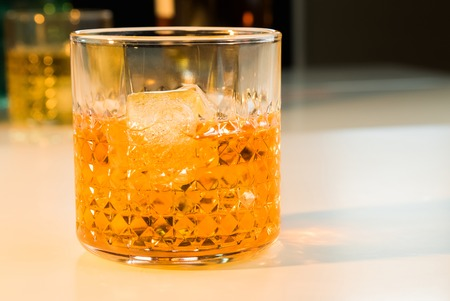 snifter: whiskey with ice cubes in glass with bottle in background, whisky relax time  concept