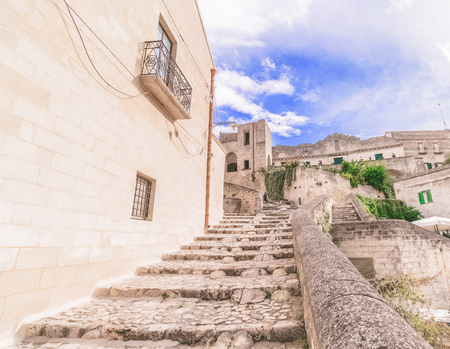 typical old stairs view of Matera under blue sky .