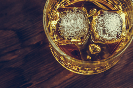top of view of whiskey in glass with ice cubes on wood table background,  focus on ice cubes, whisky relax time