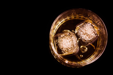 snifter: top of view of whiskey in the glass with ice cubes on black background, focus on ice cubes, whisky relax time Stock Photo