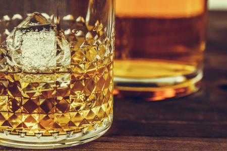 atmosphere: glass of whiskey with ice cubes near bottle on wood table, warm atmosphere, time of relax with whisky Stock Photo