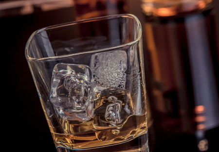 snifter: close-up of whiskey with ice cubes in glass near bottle on black background, warm atmosphere, time of relax with whisky Stock Photo