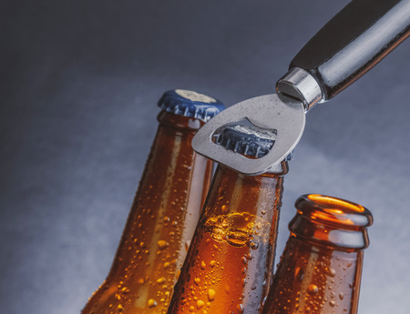 bottle cap opener: three fresh cold beer ale bottles with drops and stopper open with bottle opener on dark background Stock Photo