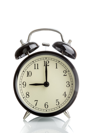 its nine oclock already, time to wake up for breakfast, vintage old black metallic alarm clock white background