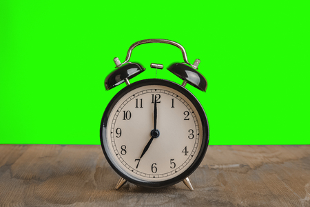 its seven oclock already, time to wake up for breakfast, vintage old black metallic alarm clock on wood table and chroma key green screen background