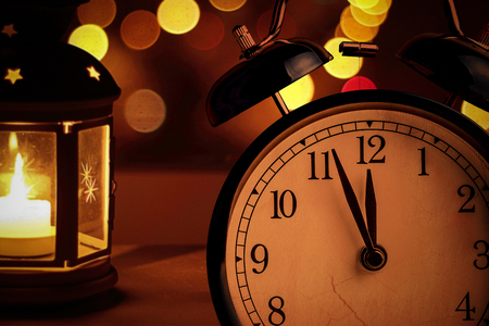 vintage alarm clock is showing midnight. It is twelve oclock, christmas and bokeh, holiday happy new year festive concept on light lantern background