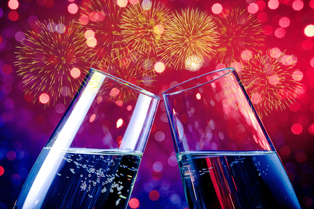 champagne flutes with golden bubbles make cheers on red and purple light bokeh and fireworks sparkle background, happy new year valentine day concept