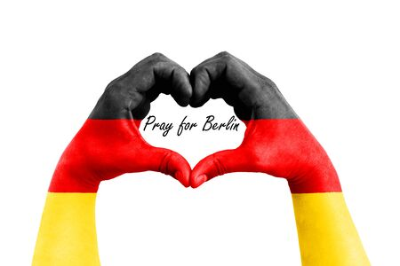 hopeful: pray for berlin, germany, man hands in the form of heart with the flag of germany on the white background, concept for hope and helpful support for the berlin victims Stock Photo