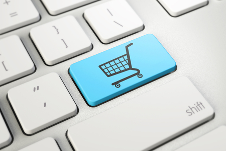 shopping cart symbol on blue button key of white keyboard, online shopping, internet shop concept