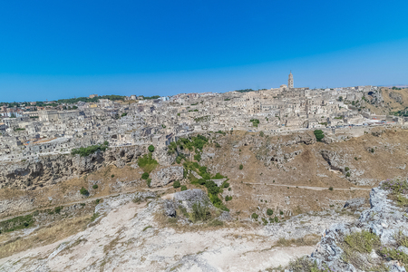 panoramic view of typical stones (Sassi di Matera) and church of Matera UNESCO European Capital of Culture 2019 under blue sky. Basilicata, Italy