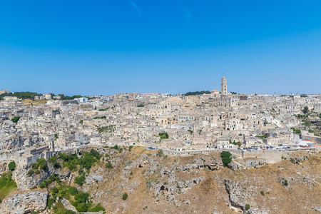 di: panoramic view of typical stones (Sassi di Matera) and church of Matera UNESCO European Capital of Culture 2019 under blue sky. Basilicata, Italy
