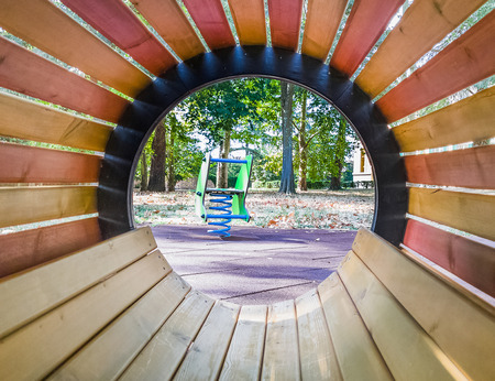 see through empty wood tube at playground for child, on green meadow background