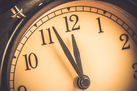 old grunge vintage alarm clock is showing midday or midnight movement. It is twelve oclock, holiday happy new year festive and christmas or lunch concept