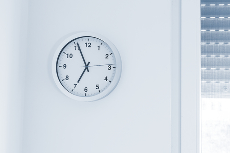 its seven oclock already, time to wake up for breakfast, modern white metallic alarm clock on modern white wall background
