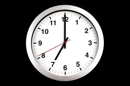 its seven oclock already, time to wake up for breakfast, modern white metallic alarm clock on black background