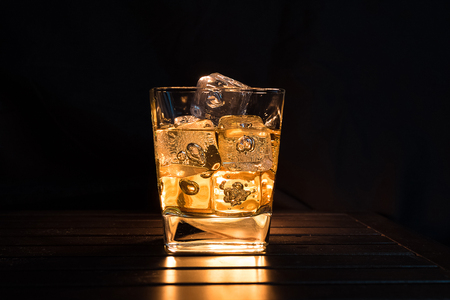 whiskey with ice cubes in glass on dark background and wood table, relax with whisky concept on the warm atmosphere Standard-Bild - 100560989