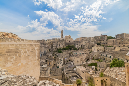 panoramic view of typical stones Sassi di Matera and church of Matera under blue sky with clouds Standard-Bild - 100868634
