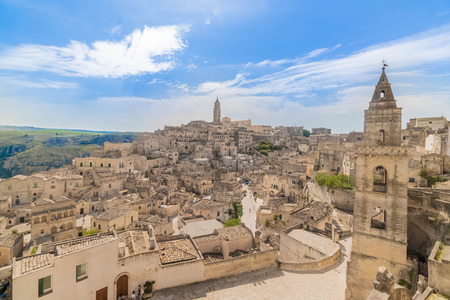 panoramic view of typical stones Sassi di Matera and church of Matera under blue sky with clouds Standard-Bild - 100932718