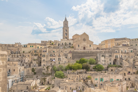 panoramic view of typical stones Sassi di Matera and church of Matera under blue sky with clouds Standard-Bild - 101361389