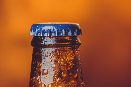 close-up of fresh cold beer ale single bottle with drops and stopper on warm background Фото со стока