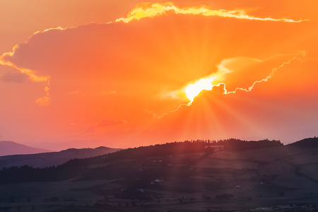 sunset scene with sun fall behind the clouds and mountains in background, warm colorful sky with soft clouds Standard-Bild - 107781211