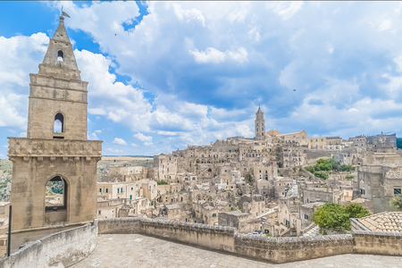 panoramic view of typical stones (Sassi di Matera) and church of Matera UNESCO European Capital of Culture 2019 under blue sky white clouds, Basilicata, Italy Standard-Bild - 107781212