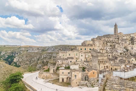 panoramic view of typical stones (Sassi di Matera) and church of Matera UNESCO European Capital of Culture 2019 under blue sky white clouds, Basilicata, Italy Standard-Bild - 107668862