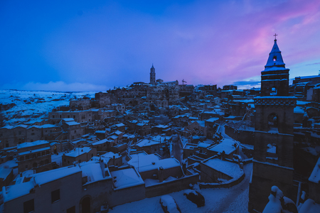 panoramic view of typical stones Sassi di Matera and church of Matera 2019 under blue sky with clouds and snow on the house, concept of travel and christmas holiday on snowflakes at night,capital of europe culture 2019