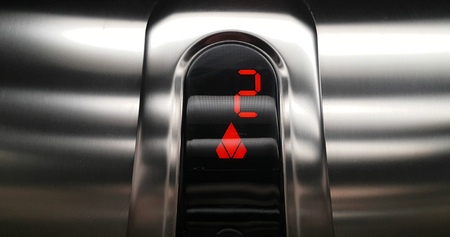 detail of red led with number two of elevator that go up from second to third floor, business and technology  concept