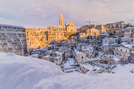 panoramic view of typical stones Sassi di Matera and church of Matera 2019 under blue sky with clouds and snow on the house, concept of travel and christmas holiday on snowflakes at sunset,capital of europe culture 2019