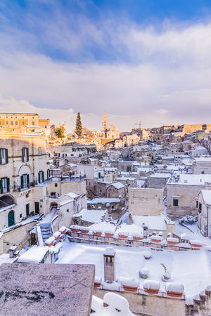 panoramic view of typical stones Sassi di Matera and church of Matera 2019 under blue sky with clouds and snow on the house, concept of travel and christmas holiday on snowflakes,capital of europe culture 2019