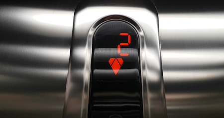 detail of red led with number two of elevator that go up from second to first floor, business and technology  concept