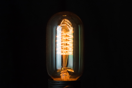 turn on retro vintage light bulb with tungsten technology built-in on black background, old style atmosphere concept