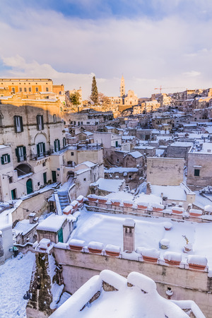 panoramic view of typical stones Sassi di Matera and church of Matera 2019 under blue sky with clouds and snow on the house, concept of travel and christmas new year holiday on snowflakes,capital of europe culture 2019