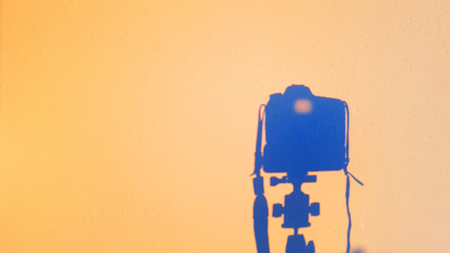 silhouette of camera reflex on the wall at sunset, concept of technology photography equipment