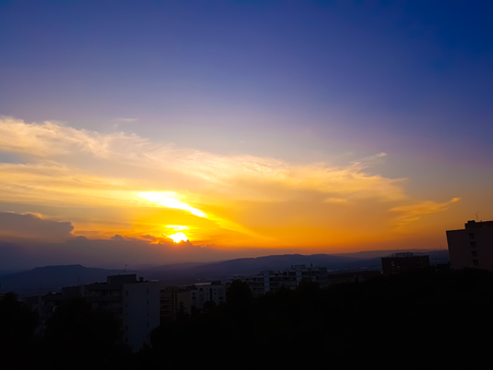 sunset scene with sun fall behind the clouds and mountains in background, warm colorful sky with soft clouds