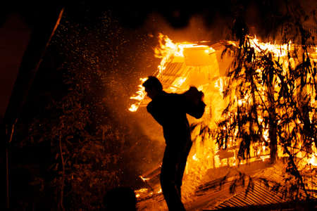 People are trying to extinguish a house fire by throwing water. Stock Photo