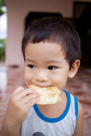 Asian boy eating candy Stock Photo