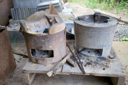 Old clay stove covered by rusted zinc jacket for traditional cooking in Thailand photo
