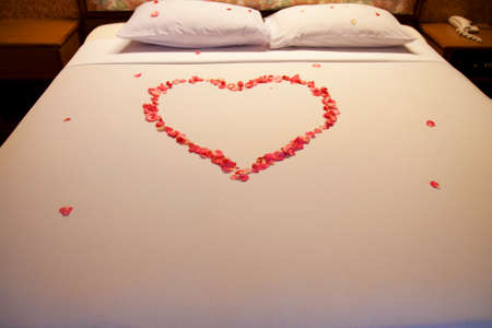 Honeymoon bed decorated with red rose petals and towels photo