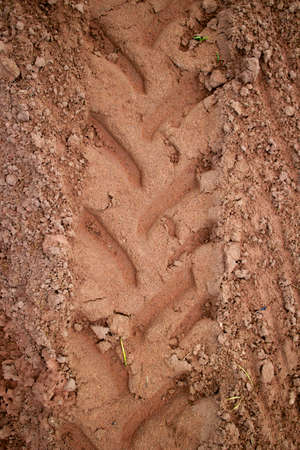 Tractor trail closeup on the muddy ground after rain photo