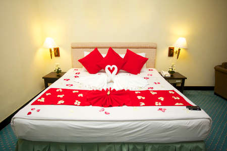 heart suite: Red heart pillows and two towel swans shaped on the bed,Honey moon bed   Stock Photo