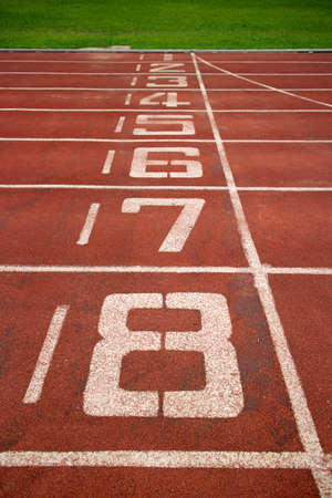 Red treadmill at the stadium with the numbering from one to eight photo
