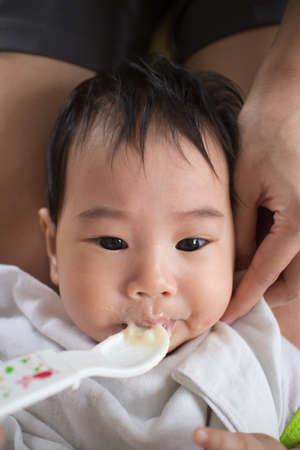 Asians eat babies mouth mess forced to eat. photo