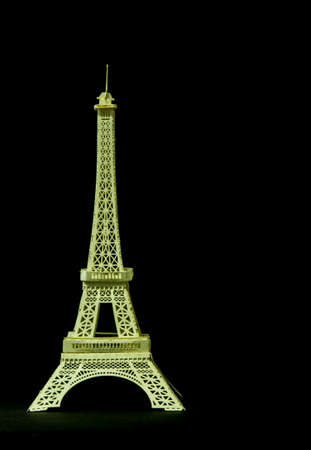 A model Eiffel tower paper toy display on black background Фото со стока