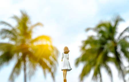 girl toy figure back view in green beach Banco de Imagens