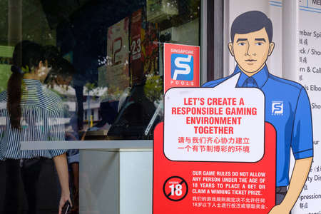 Singapore-22 FEB 2019: Customers buy lottery tickets in Singapore Pools shop