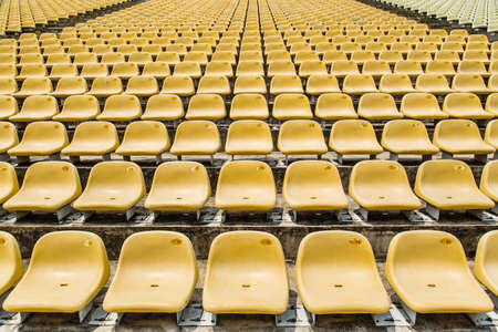 many yellow empty chairs on the outdoor stadium