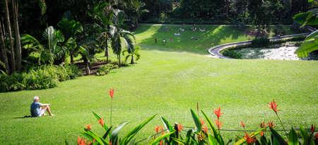 Singapore-16 JUN 2018:old man sit on the big lawn in Singapore botanic garden